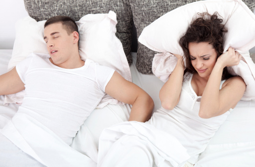 Photo of a woman having a hard time sleeping because a man is snoring. Learn more about sleep apnea at Bijan Family Dental Practice in Fountain Valley, CA